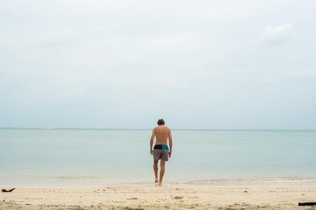 Młody człowiek chodzenie na białej, piaszczystej plaży