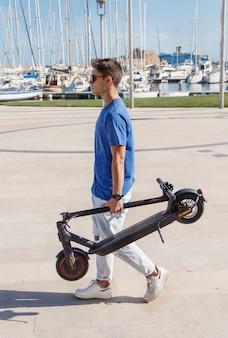Młody człowiek chodzenie ze złożonym skuterem elektrycznym przed portem jachtowym