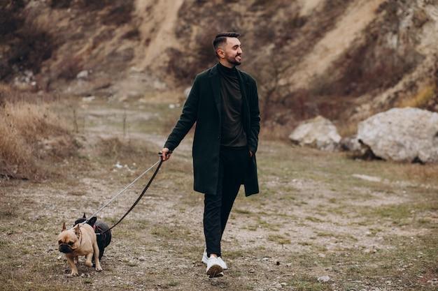 Młody człowiek chodzi jego francuskiego buldoga w parku