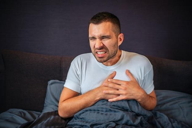 Młody człowiek cierpi na atak ciepła. trzyma ręce w tym miejscu. kurczy się. młody człowiek czuje się okropnie. siedzi na łóżku z zakrytą dolną częścią ciała.