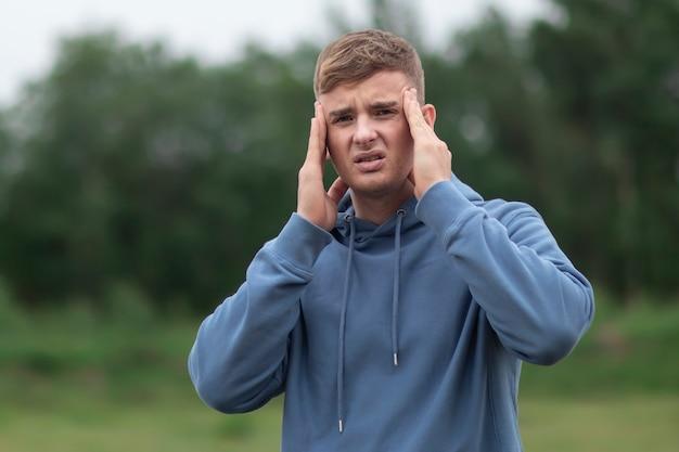 Młody człowiek cierpi na ból głowy