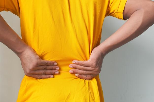 Młody człowiek cierpi na ból pleców z bliska