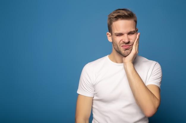 Młody człowiek cierpi na ból zęba na niebieskim tle