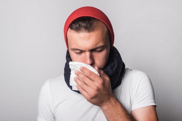 Młody człowiek cierpi na przeziębienie i grypę na szarym tle