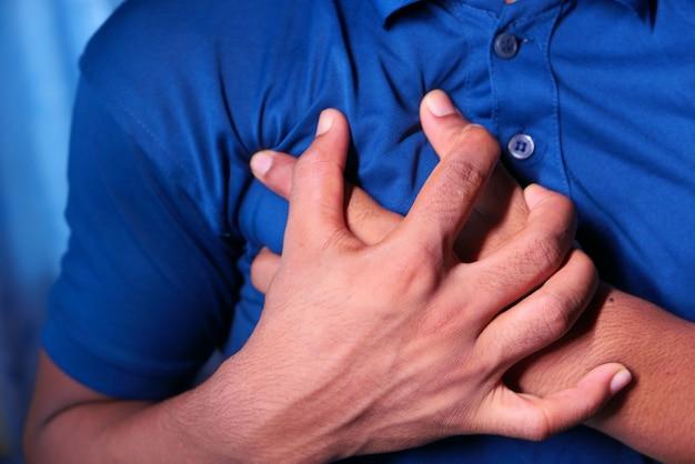 Młody człowiek cierpi na serce i trzyma jego klatkę piersiową.
