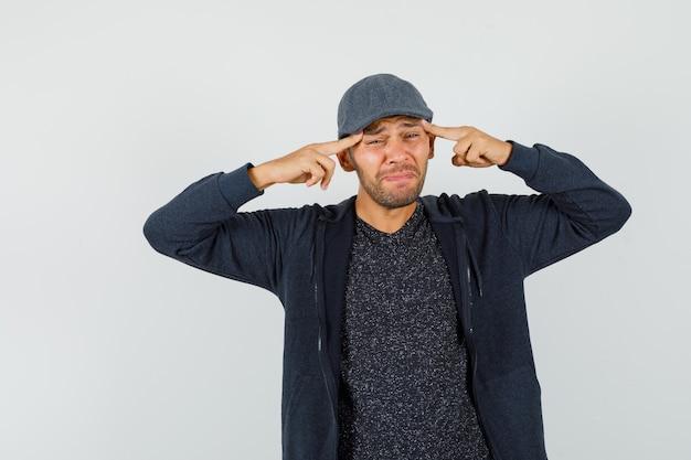 Młody człowiek cierpiący na bolesną migrenę w koszulce, kurtce, czapce i smutny wygląd