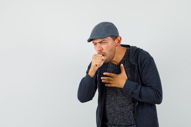 Młody człowiek cierpiący na kaszel w koszulce, kurtce, czapce i źle wyglądający