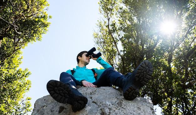 Młody człowiek cieszący się widokami z lornetką na szczycie góry
