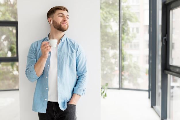 Młody człowiek cieszy się filiżankę kawy