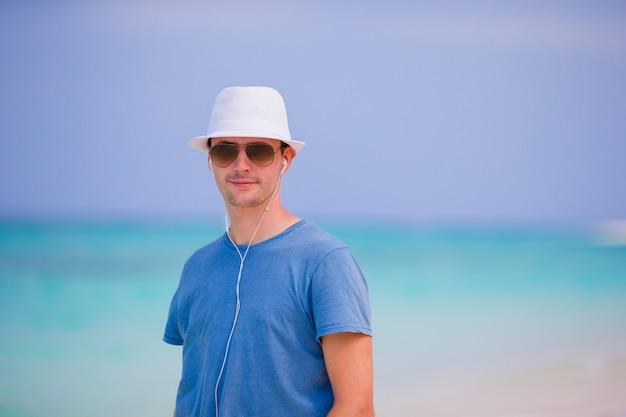Młody człowiek cieszy się muzykę na białej piaskowatej plaży