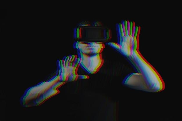 Młody człowiek cieszy się okularami wirtualnej rzeczywistości. czarno-biały z efektem wirtualnej rzeczywistości 3d glitch