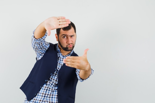 Młody człowiek co gest ramy w koszuli, kamizelce i patrząc skoncentrowany, widok z przodu.
