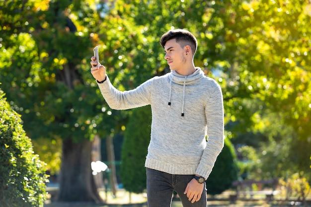 Młody człowiek co selfie w parku w zimny słoneczny dzień
