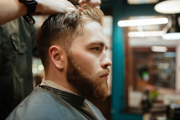 Młody człowiek coraz strzyżenie przez fryzjera nożyczkami, siedząc na krześle.