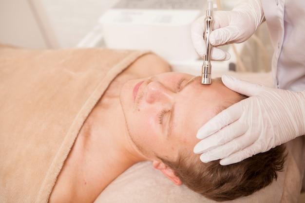 Młody człowiek coraz zabieg pielęgnacji skóry twarzy przez kosmetologa