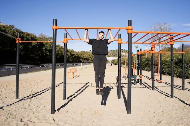 Młody człowiek ćwiczenia na barach na zewnątrz. koncepcja fitness, sportu, treningu i stylu życia - kalistenika podciąga.