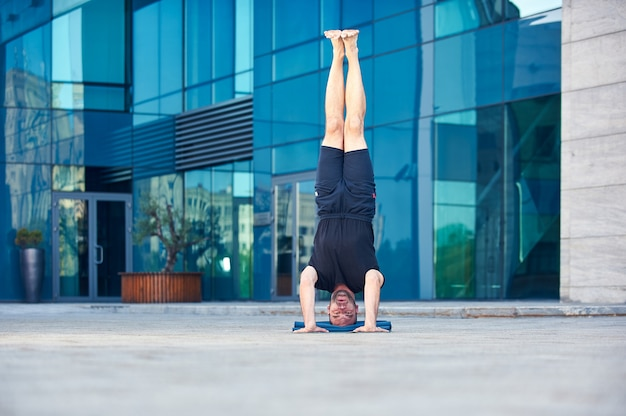 Młody człowiek ćwiczy asana jogi na głowie sirsasana stanowią na zewnątrz
