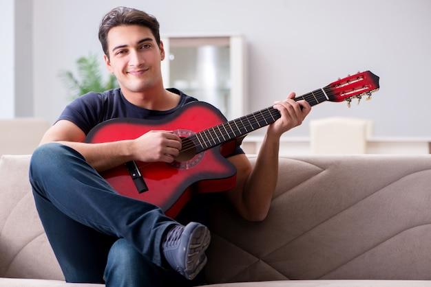 Młody człowiek ćwiczy bawić się gitarę w domu