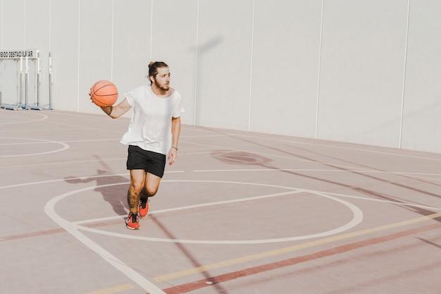 Młody człowiek ćwiczy koszykówkę