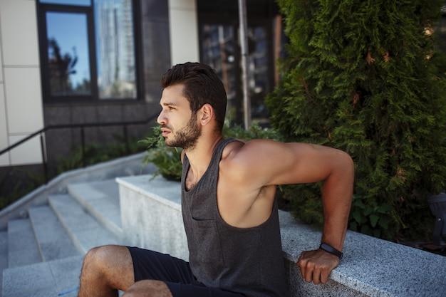 Młody człowiek ćwiczy na zewnątrz. facet robi odwrócone pompki trzymając ręce za plecami.