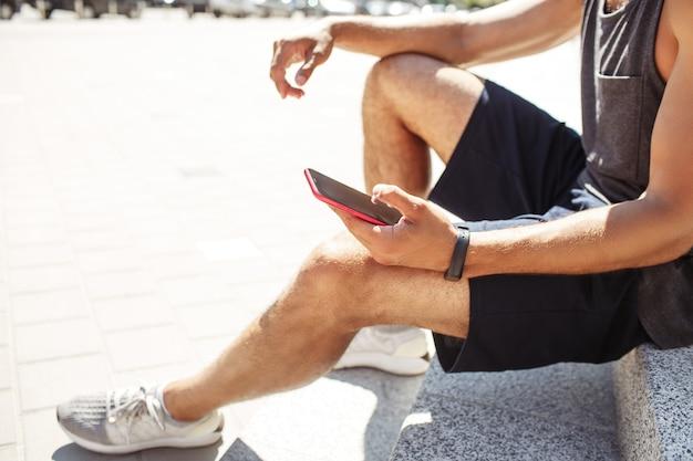 Młody człowiek ćwiczy na zewnątrz. wytnij widok z boku sportowego faceta, trzymając w ręku telefon. monitor aktywności na nadgarstku. odpocznij po treningu lub treningu. nowoczesne technologie i urządzenia.