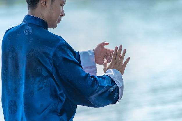 Młody człowiek ćwiczy tradycyjnego tai chi chuan, tai ji i qi gong, chińskie sztuki samoobrony.