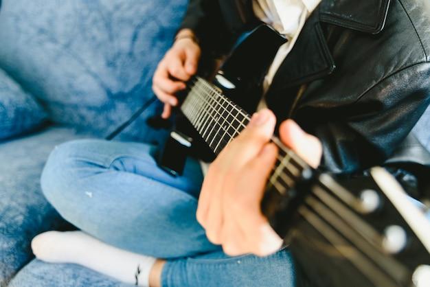 Młody człowiek ćwiczy z jego gitarą elektryczną na kanapie jego domowa uczenie.