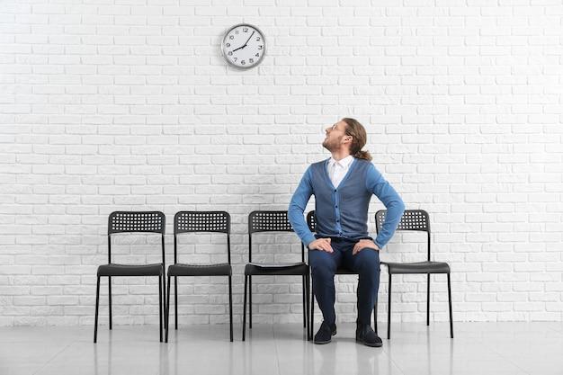 Młody człowiek czeka na rozmowę kwalifikacyjną w pomieszczeniu