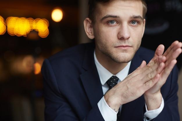 Młody człowiek czeka w kawiarni