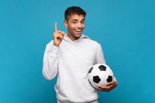 Młody człowiek czujący się jak szczęśliwy i podekscytowany geniusz po zrealizowaniu pomysłu, radośnie podnoszący palec, eureka !. koncepcja piłki nożnej