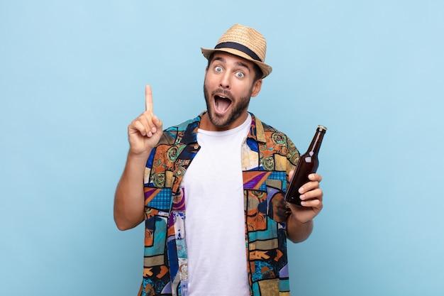 Młody człowiek czujący się jak szczęśliwy i podekscytowany geniusz po zrealizowaniu pomysłu, radośnie podnoszący palec, eureka !. koncepcja wakacji