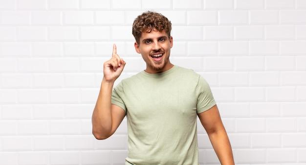 Młody człowiek czujący się jak szczęśliwy i podekscytowany geniusz po zrealizowaniu pomysłu, radośnie podnoszący palec, eureka!