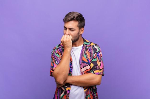 Młody człowiek czujący się poważnie, zamyślony i zatroskany, wpatrzony w bok z ręką przyciśniętą do brody
