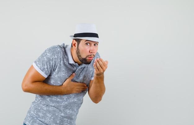 Młody człowiek czuje mdłości w koszulce, kapeluszu i wygląda na chorego, widok z przodu.