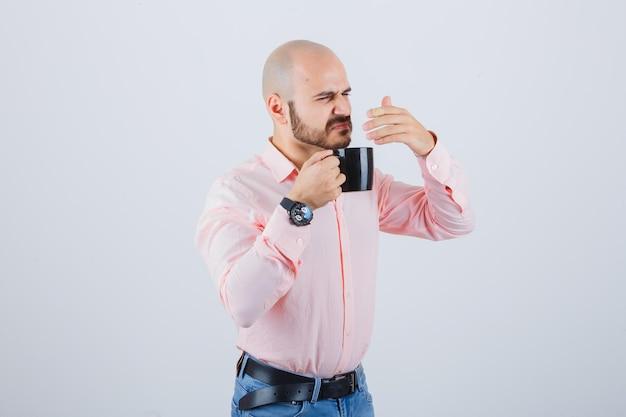 Młody człowiek czuje nieprzyjemny zapach w różowej koszuli, dżinsach i wygląda na zdegustowanego. przedni widok.