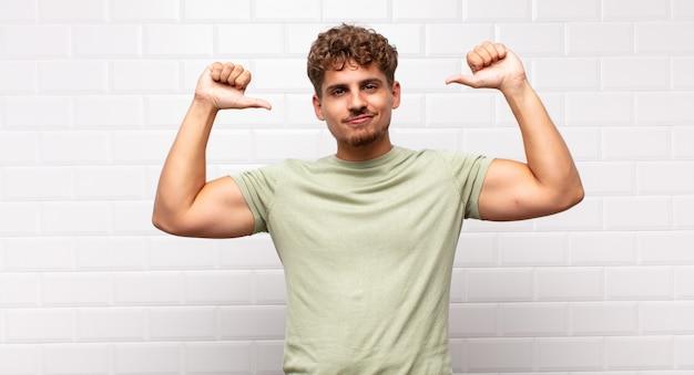 Młody człowiek czuje się dumny, arogancki i pewny siebie, wygląda na zadowolonego i odnoszącego sukcesy, wskazuje na siebie