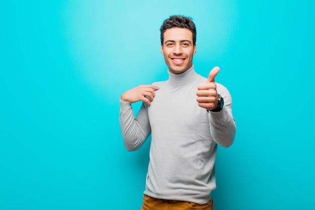Młody człowiek czuje się dumny, beztroski, pewny siebie i szczęśliwy, uśmiechając się pozytywnie z kciukami do góry nad ścianą