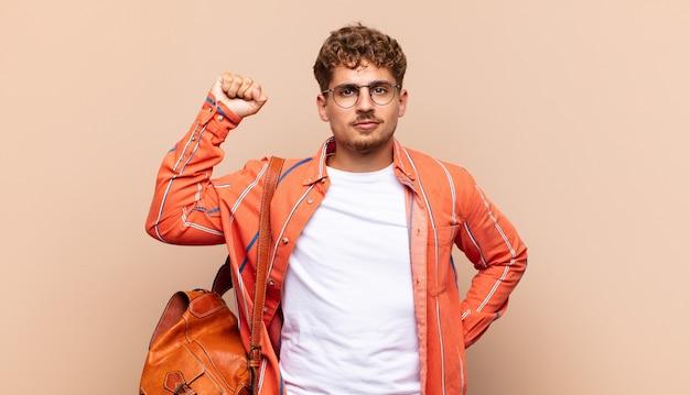 Młody człowiek czuje się poważny, silny i zbuntowany, podnosi pięść, protestuje lub walczy o rewolucję. koncepcja studenta