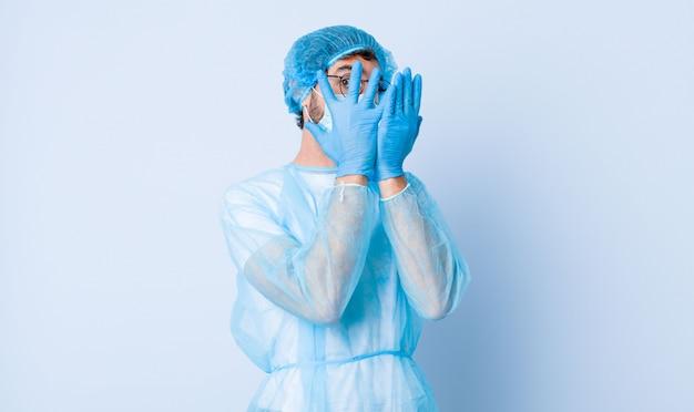 Młody człowiek czuje się przestraszony lub zawstydzony, zerkając lub szpiegując oczy na wpół pokryte rękami. koncepcja koronawirusa