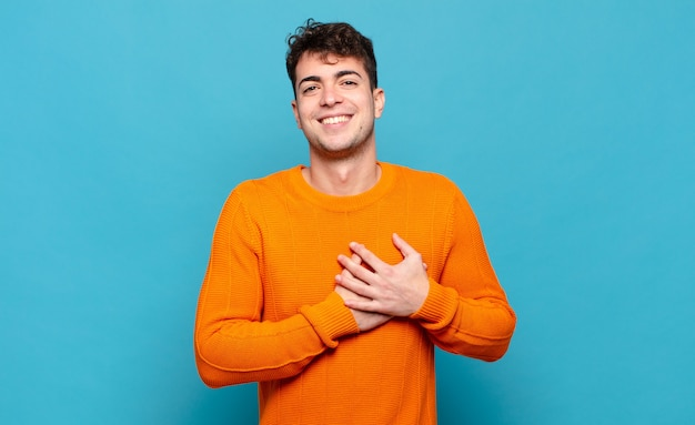 Młody człowiek czuje się romantyczny, szczęśliwy i zakochany, uśmiecha się radośnie i trzyma ręce blisko serca