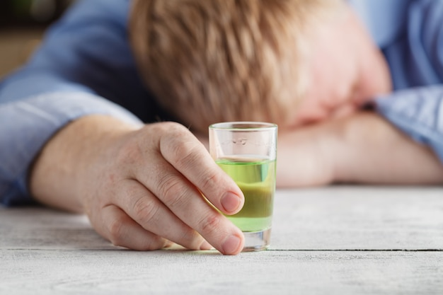 Młody człowiek czuje się samotny i pije za dużo alkoholu we własnym domu przy stole
