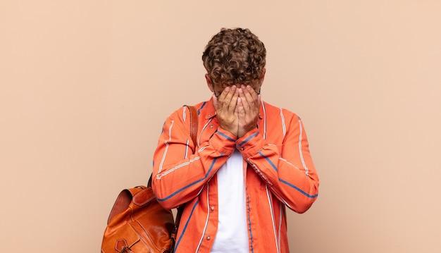 Młody człowiek czuje się smutny, sfrustrowany, zdenerwowany i przygnębiony, zakrywa twarz obiema rękami, płacze. koncepcja studenta