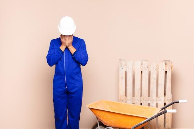 Młody człowiek czuje się smutny, sfrustrowany, zdenerwowany i przygnębiony, zakrywając twarz obiema rękami, płacząc koncepcja budowy