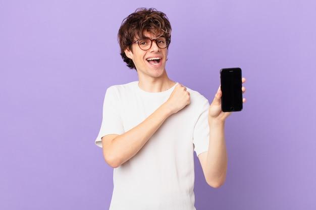 Młody człowiek czuje się szczęśliwy i staje przed wyzwaniem lub świętuje i trzyma komórkę