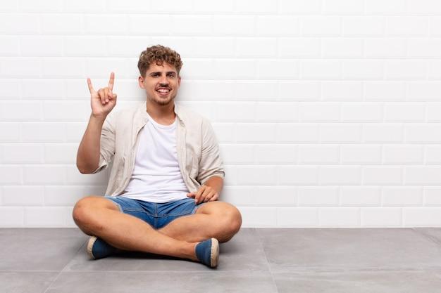 Młody człowiek czuje się szczęśliwy, zabawny, pewny siebie, pozytywny i zbuntowany, robi ręką znak rocka lub heavy metalu