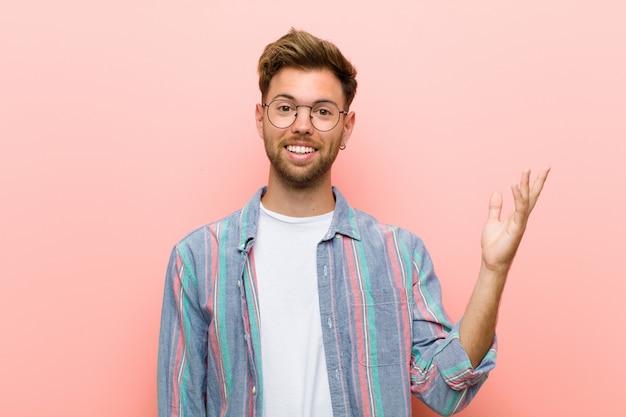 Młody człowiek czuje się szczęśliwy, zaskoczony i wesoły, uśmiechając się z pozytywnym nastawieniem, realizując rozwiązanie lub pomysł na różowym tle
