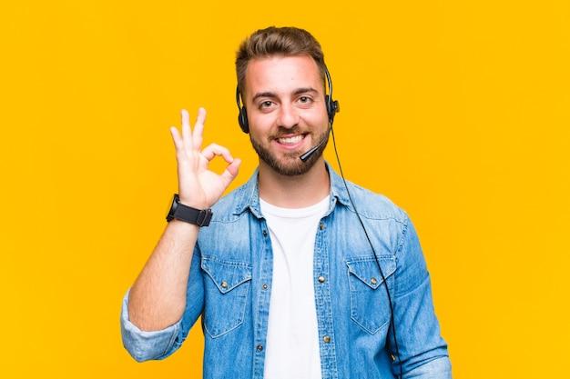 Młody człowiek czuje się szczęśliwy, zrelaksowany i usatysfakcjonowany, okazując aprobatę w porządku gestem, uśmiechając się