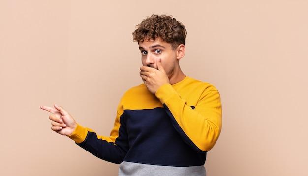Młody człowiek czuje się szczęśliwy, zszokowany i zaskoczony, zakrywając usta dłonią i wskazując na boczną przestrzeń kopii