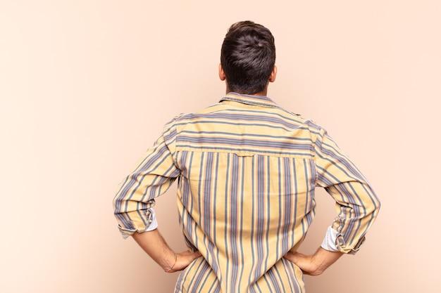 Młody człowiek czuje się zagubiony lub pełny lub ma wątpliwości i pytania, zastanawiając się, z rękami na biodrach, widok z tyłu