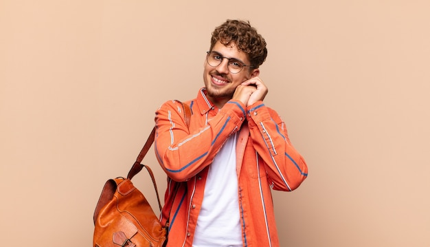 Młody człowiek czuje się zakochany i wygląda słodko, uroczo i szczęśliwie, romantycznie uśmiecha się z rękami obok twarzy. koncepcja studenta